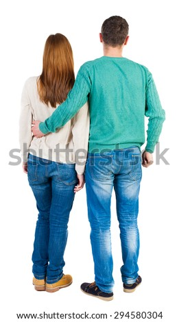 Back view of young embracing couple (man and woman) hug and look into the distance.  backside view of person.  Isolated over white background. The guy in the green jacket hugging his girlfriend.
