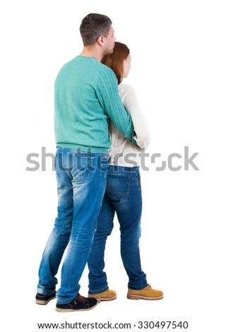 Back view of young embracing couple (man and woman) hug and look into the distance. beautiful friendly girl and guy together. Rear view people collection.  backside view of person.  I