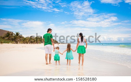 Back view of young family looking to the sea in Mexico beach - stock photo