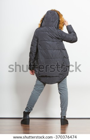 Back view of young fashionable girl wearing jacket with hood. Fashion in winter time.