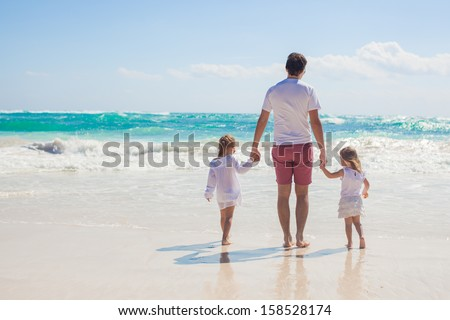 Back view of Young father and his adorable little daughters walking on white sand beach in sunny day - stock photo