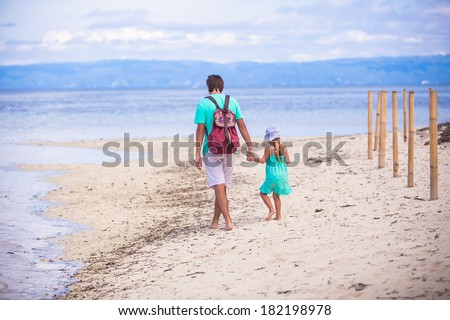 Back view of young father and his little girl walking by the sea - stock photo