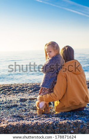 Back view of Young father and little girl at the beach on a sunny winter day - stock photo