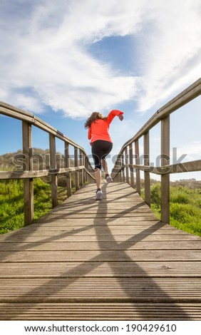 Back view of young girl running in training over wood boardwalk on a sunny day - stock photo