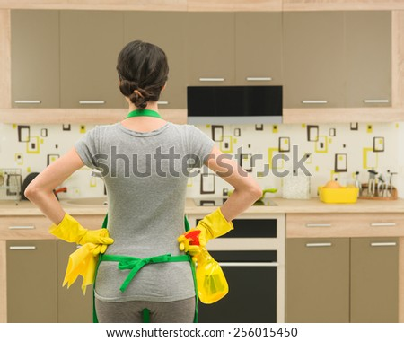 back view of young housewife getting ready for kitchen cleaning - stock photo