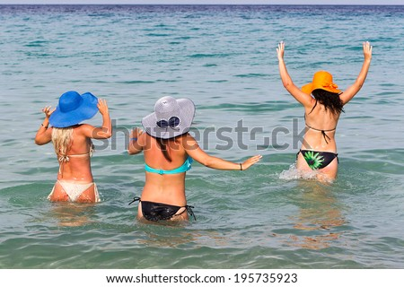 Back View of young ladies getting into tropical sea in summer hats