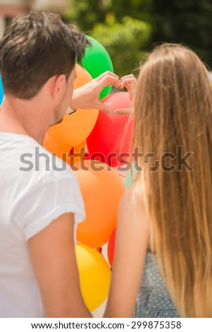 Back view of young lovely couple with balloons shaping heart symbol with hands.