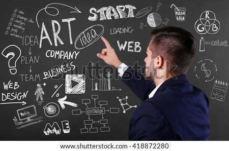 Back view of young man in navy suit pointing on blackboard. Start up concept