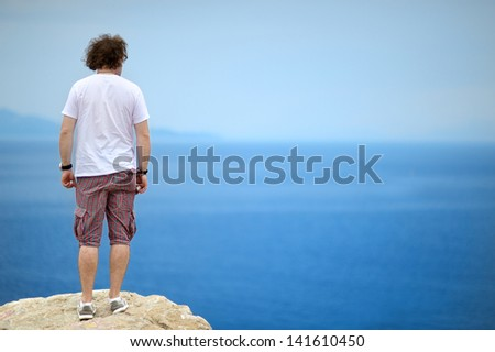 Back view of young man looking to the ocean