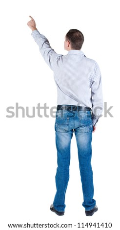 Back view of young man pointing at wall. Rear view people collection.  backside view of person.  Isolated over white background.