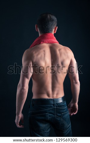 Back view of young man shirtless with red towel against black background.