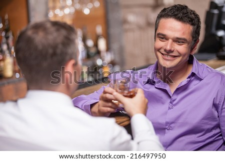 back view of young man talking at counter. two friends sitting in bar and drinking whisky - stock photo