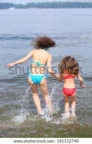 Back view of young mother and daughter jumping in water holding hand