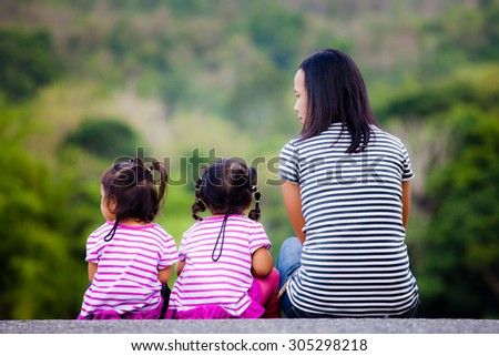 Back view of young mother and daughter sitting on ground - stock photo