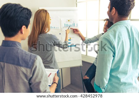 Back view of young people of different nationalities discussing business affairs while examining graphs - stock photo