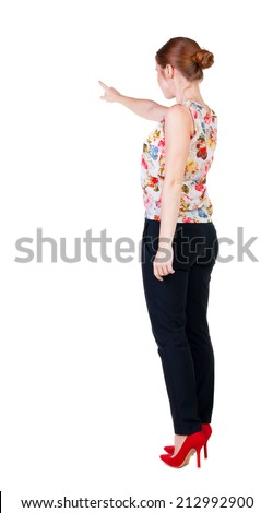 Back view of young redhead business woman pointing at wall. beautiful girl in dark suit. Rear view people collection. backside view of person. Isolated over white background. - stock photo