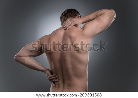 back view of young shirtless man with neck pain. young man standing on grey white background - stock photo