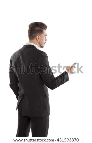 Back view of young stylish businessman isolated on white background using smart phone - stock photo