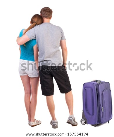 Back view of young traveling couple with suitcas.  Rear view. Isolated over white background. Sports heterosexual couple hugging in summer shorts