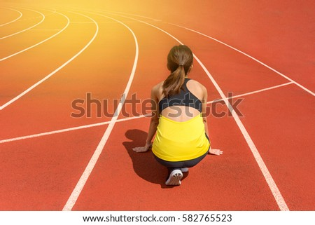 Back View Of Young Woman Athlete At Starting Position Ready To Start A Race Female