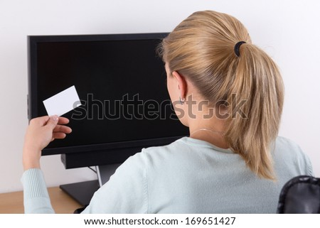 back view of young woman holding visiting card and using pc with copyspace on the screen