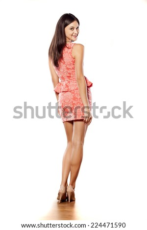 back view of young woman in a tight orange dress posing on white - stock photo