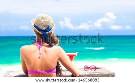 back view of young woman in bikini and straw hat with strawberry margarita cocktail on beach. Tulum, Mexico