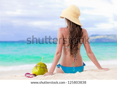 back view of young woman in bikini with fresh coconut - stock photo