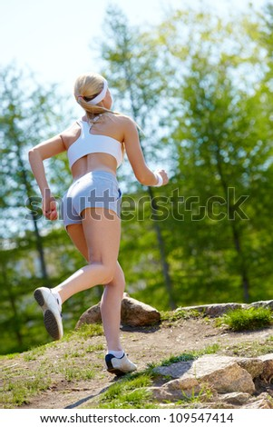 Back view of young woman jogging outside