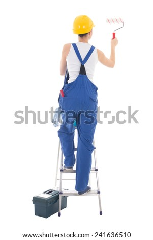 back view of young woman painter in blue coveralls standing on ladder isolated on white background - stock photo