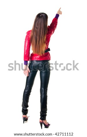 Back view of young woman points at wall. The rear view. Isolated over white