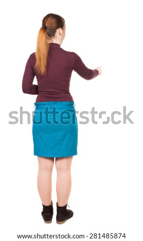 back view of young woman presses down on something. Isolated over white background. Rear view people collection. backside view of person. Low girl in a blue skirt right thumb presses the button. - stock photo