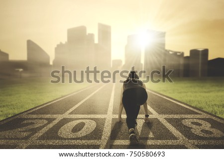 Back view of young woman ready to run toward a city while kneeling on the road with numbers 2018