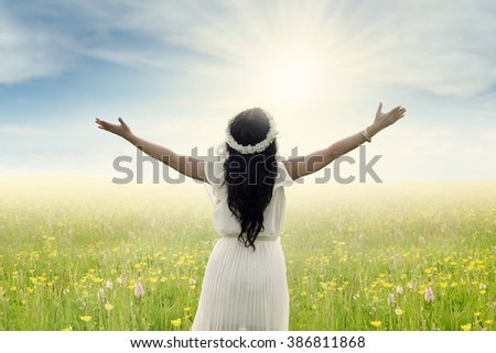 Back view of young woman standing on the meadow with outstretched hands, shot in springtime