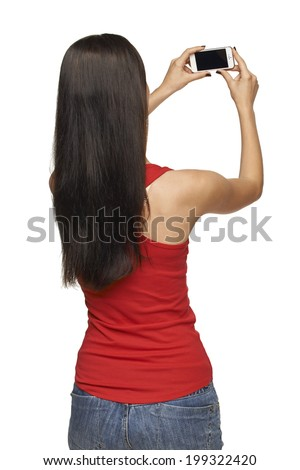 Back view of young woman taking pictures through cell phone, over white background