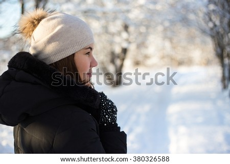 back view of young woman walking in snowy winter forest