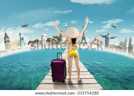 Back view of young woman wearing swimwear on the bridge and enjoy holiday to the worldwide monuments - stock photo