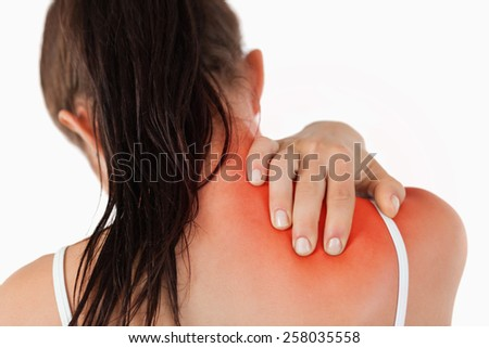 Back view of young woman with neck pain against a white background - stock photo
