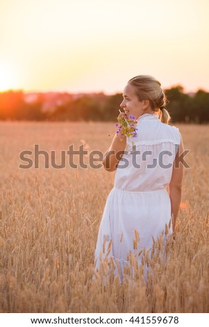 Back view on beautiful young woman walking on the rye field at sunset. Happy girl enjoying countryside life. Sunset on a farm. Lifestyle concept - stock photo