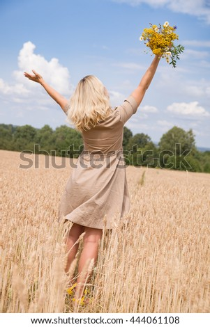 Back view on happy woman with flowers running on the wheat field and enjoying sun. Summer and blue sky background. Girl walking on the meadow. Lifestyle and happiness, freedom concept - stock photo