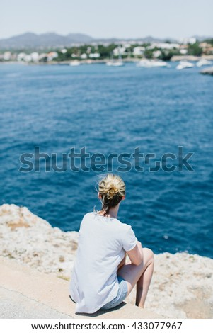 Back view on woman with tied hair, shorts and gray shirt looking over while seated on stones at waterfront with copy space