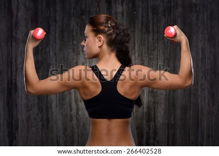 Back view photo of young mixed race sporty woman wearing black tracksuit for training. She holding red dumbbells and looking to the left. Fitness concept - stock photo