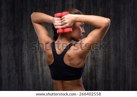 Back view photo of young mixed race sporty woman wearing black tracksuit for training. She holding red dumbbells and demonstrating back muscles. Fitness concept - stock photo