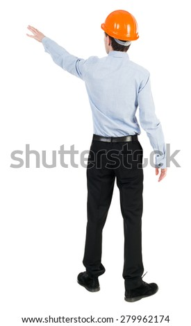 Back view pointing young men in  shirt and helmet. Young guy  gesture. Rear view people collection.  Isolated over white background. Young engineer in shirt and black trousers indicates left hand.  - stock photo