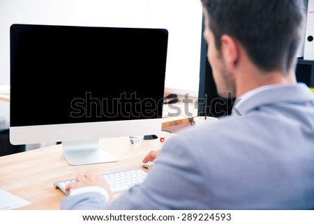 Back view portrait of a businessman sitting at the table with blank monitor