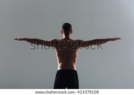 Back view portrait of a fitness man workout with arms at the sides over gray background - stock photo