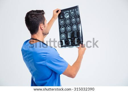Back view portrait of a male doctor looking at x-ray picture of brain isolated on a white background - stock photo