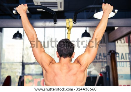 Back view portrait of a man tightening at gym - stock photo