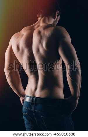 Back view portrait of a man with muscular body posing on black background
