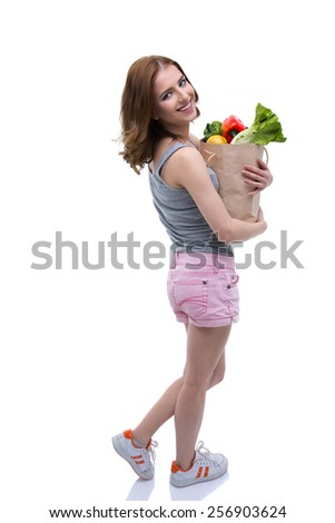 Back view portrait of a smiling woman holding a shopping bag full of groceries - stock photo